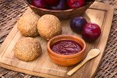 stock photo of satsuma  - Small wooden bowl of plum jam with wholegrain buns and satsuma plums on wooden board photographed with natural light  - JPG