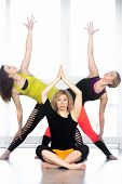 pic of extend  - Group of beautiful females in different yoga asana in class middle aged woman sitting in sukhasana girls on the background standing in Extended Triangle Pose  - JPG