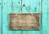 Blank antique wood sign hanging on distressed blue green door