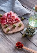 Jamon With Capers And Olives On The Wooden Board