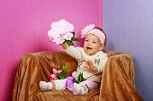 Little girl in the chair with flowers