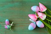 Colorful decorative easter eggs and branch with spring flowers on the old wooden background