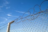 Metal Fence With Barbed Wire Over Blue Sky