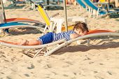 Toddler Dressed As A Sailor Lying On A Sunbed On A Beach. Photo With Untraditional Color Rendering F