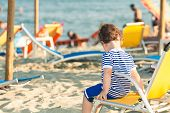 Toddler Dressed As A Sailor Sitting On A Beach Chair With Other People In Defocussed Background. Pho