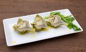 stock photo of boil  - Boiled artichokes on tray on wooden table - JPG