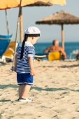 Toddler Dressed As A Sailor Walking On A Beach. Photo With Untraditional Color Rendering For Artisti