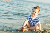 Toddler With Sailor Shirt Playing With A Car At The Edge Of The Water On A Beach. Photo With Untradi
