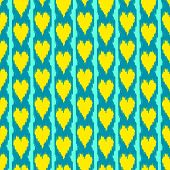 Colorful heart shape ikat seamless pattern in blue and yellow, vector