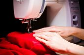 Female hands by working on sewing machine