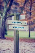 Rustic Wooden Sign In An Autumn Park With The Words Careful - Careless