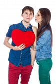 Eautiful young happy couple kissing behind a red heart, holding it in hands, isolated on a white bac