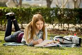 foto of denim jeans  - young beautiful student girl lying on campus park grass with books on rug studying happy preparing exam in university and college education concept - JPG