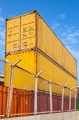 Metal Cargo Containers Are Stacked Under Blue Cloudy Sky
