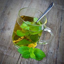 foto of peppermint  - glas of peppermint tea on wooden table - JPG