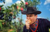 stock photo of cowboy  - Young cowboy eats red apple in garden - JPG