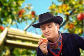 image of cowboy  - Young cowboy has picked red apple in farm and eats it - JPG