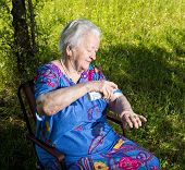 pic of insect  - Old woman spraying insect repellent on skin outdoor - JPG