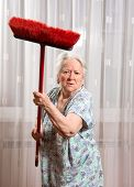 stock photo of broom  - Old angry woman threatening with a broom at home - JPG