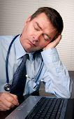 Tired Doctor Sleeps At Desk