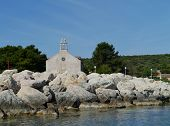 stock photo of graveyard  - The Krijal church with the graveyard situated at the harbor of the little island Premuda in the northern Adriatic sea of Croatia - JPG