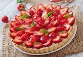 image of tarts  - Tart with strawberries and whipped cream decorated with mint leaves - JPG