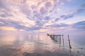 picture of marsala  - Old and damaged wooden jetty with romantic colorful cloudscape at dusk on the coastline of Sulawesi Indonesia - JPG