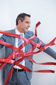 image of trap  - Businessman trapped by red tape on white background - JPG