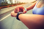picture of jogger  - young woman jogger ready to run set and looking at sports smart watch checking performance or heart rate pulse trace - JPG