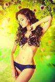 image of tropical plants  - Beautiful brunette woman in bikini among tropical plants - JPG
