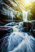 foto of waterfalls  - Tropical waterfall with sun rays - JPG