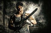 picture of man chainsaw  - Shouting muscular man with a chainsaw over dark grunge background - JPG