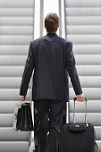 picture of trolley  - Businessman on escalator with bag and trolley - JPG