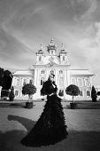 picture of evil queen  - Beautiful woman in black dress posing next to the palace - JPG
