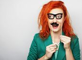 foto of mustache  - Attractive playful young woman holding mustache and glasses on a stick - JPG