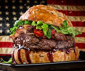 stock photo of hamburger-steak  - Delicious hamburger with fire flames and american flag on wooden background - JPG