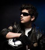 image of biker  - Portrait of handsome stylish biker over dark background - JPG