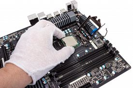 stock photo of cpu  - Installation of modern processor in CPU socket on the motherboard - JPG