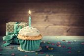 Cupcake with birthday candle and gift box poster