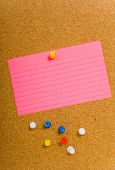 Bright, blank neon colored notecards on brown corkboard or bulletin board with plastic pushpins, space for copy