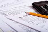 Tax prepaation items including a pencil, calculator and tax forms