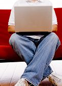 pic of futon  - A man sitting on a red couch working on a laptop computer on a white background - JPG