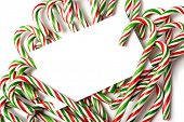 A white notecard, greeting card, or invitation surrounded by brightly color Christmas Candy Canes with copy space