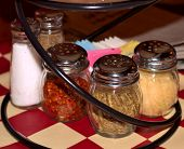 image of pizza parlor  - Spice and cheese shaker selection at pizza parlor - JPG