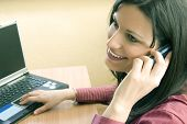 stock photo of people talking phone  - Businesswoman in her office talking on phone and laptop by her side - JPG