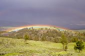 stock photo of lamar  - Surreal lighting of rainbow in storm at Lamar Valley Yellowston - JPG