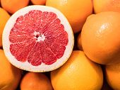 Fresh Oranges And Mandarins In A Fruit Box With A Freshly Cut Ruby Red Grapefruit poster