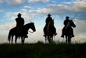 image of wild west  - Cowboys on horseback at first light - JPG