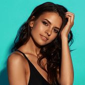 Young Sexy Slim Tanned Woman In Black Swimsuit Posing Against Blue Background. Closeup Fashion Portr poster