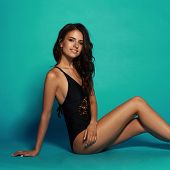 Young Sexy Slim Tanned Woman In Black Swimsuit Posing And Sitting On Blue Background. Fashion Portra poster